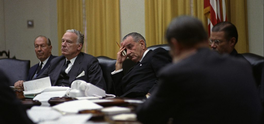 Photograph of President Johnson at an NSC meeting in 1966. He sits in the middle with two men either side. He looks bored.