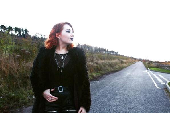 A Scottish fashion influencer poses on a rugged Scottish road