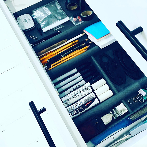 Photograph of stationery nearly arranged in a drawer.