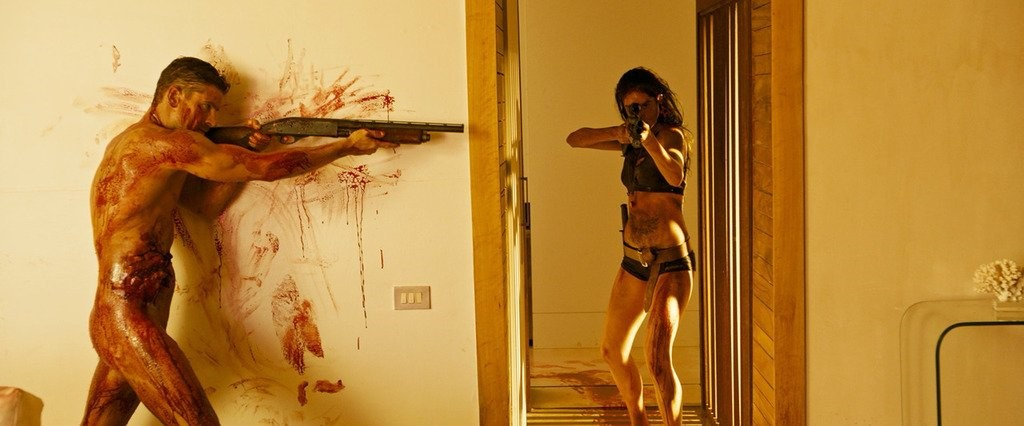 A still from film Revenge (Coralie Fargeat, 2017) showing a man and a woman with guns, both covered in blood.