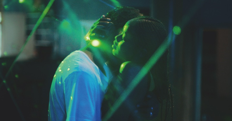 A still from film Atlantics (Mati Diop, 2019) showing a couple hugging under strong green lighting.