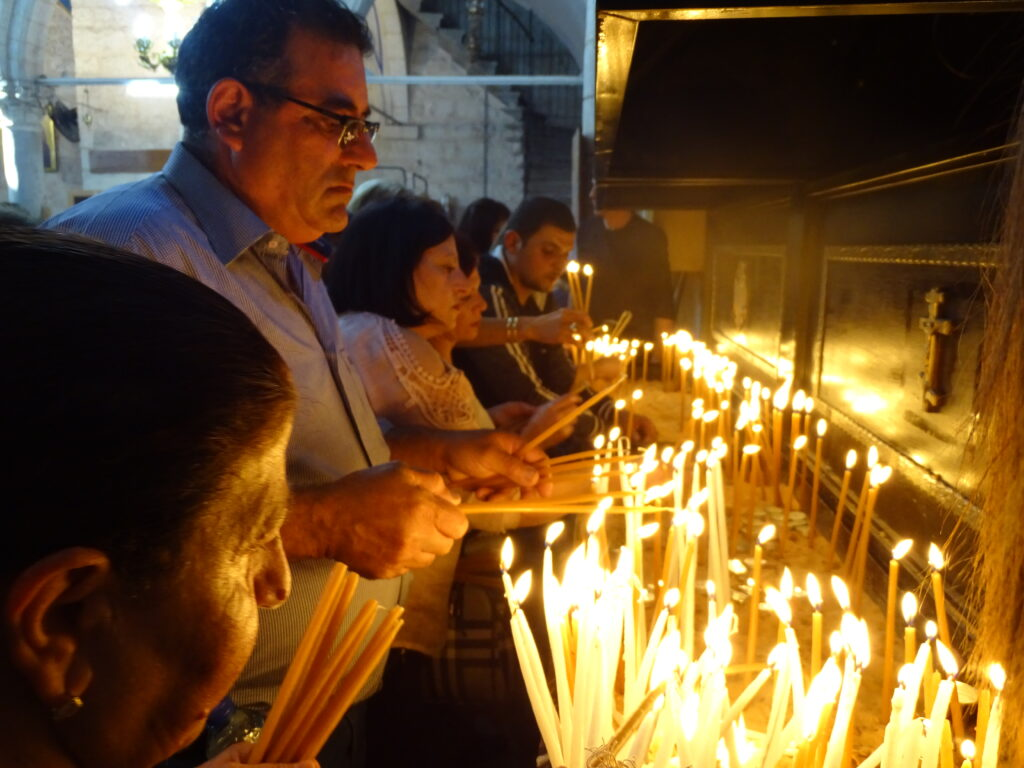 A photograph of a group of people lighting candles at the Greek Orthodox Feast of St. George in Lod, Israel