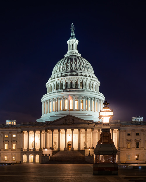 Photograph of the US Capitol building at night