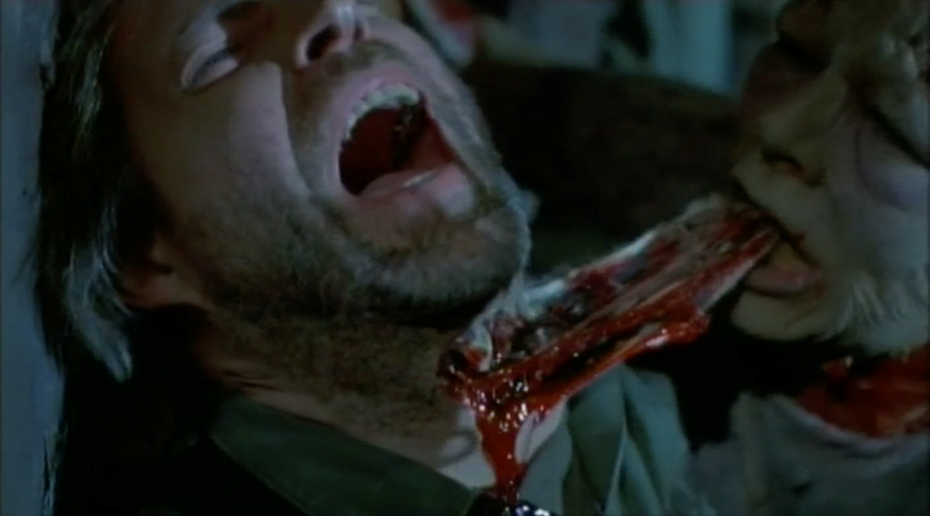A screenshot from George A. Romero's Day of the Dead (1985) showing a zombie tearing at a man's throat.