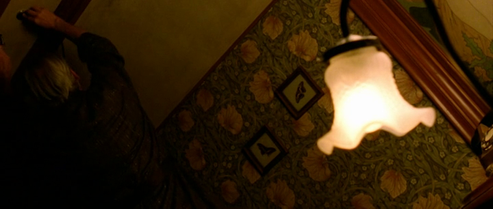 A screenshot from Hélène Cattet and Bruno Forzani's The Strange Color of Your Body's Tears (2013) showing a person in a room with patterned wallpaper.