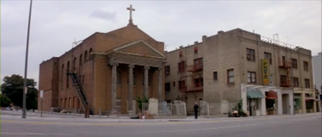 A screenshot from John Carpenter's Prince of Darkness (1987) showing a street scene with a red brick church.