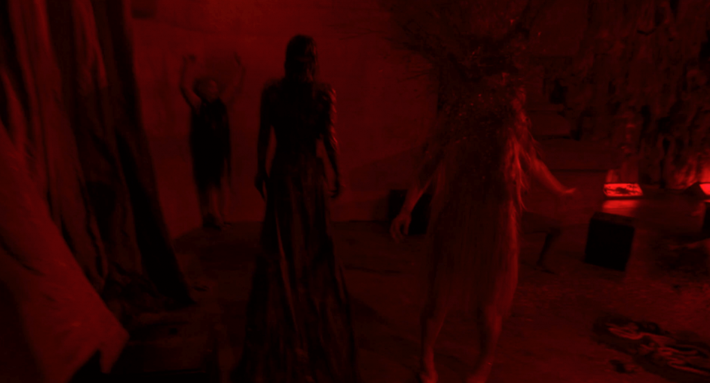 Red tinted screenshot from Luca Guadagnino's Suspiria (2018) showing three figures, one whose head is exploding with blood.