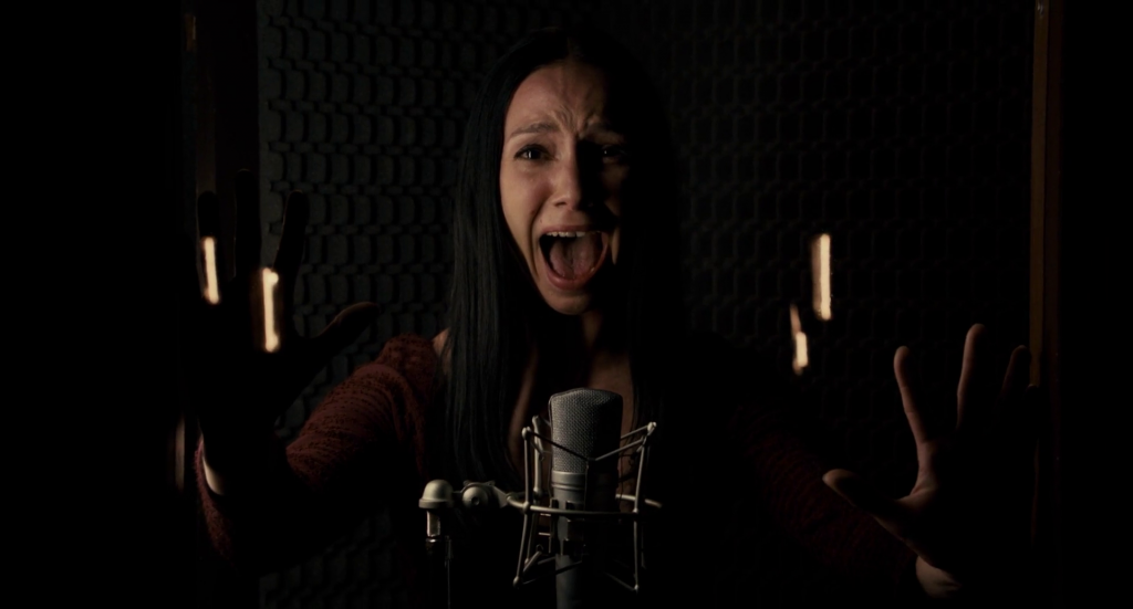 A screenshot from Peter Strickland's Berberian Sound Studio (2012) showing a woman screaming into a microphone.