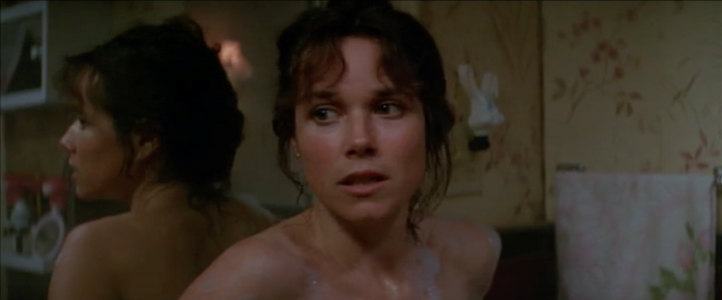 A screenshot from Sidney J. Furie's The Entity (1982) showing a nude woman looking afraid.