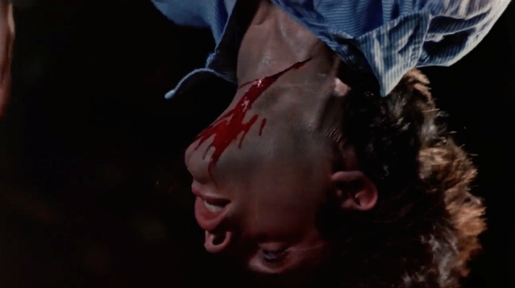 A screenshot from Steve Miner's Friday the 13th Part 2 (1981) showing a person hanging upside down with their throat cut and bleeding.