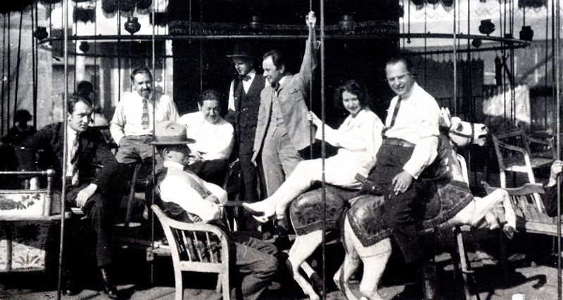 The Waxworks cast and crew relax with friends and colleagues on the film's carousel set. Paul Leni is seated fourth from left, facing the camera. From L-R: Wilhelm (William) Dieterle, Ali Hubert, E. A. Dupont, Leni, Fritz Maurischat, John Gottowt, Lore Sello, Leo Birinski. (Image: Wikimedia Commons)