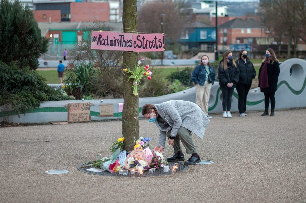 A woman lays flowers at a vigil for Sarah Everard. Photo: Tim Dennell via Wikimedia Commons