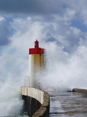 Photograph of a lighthouse on the Breton coast being hit by a large wave