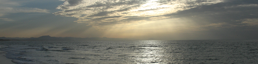 Photograph of the Breton coast, showing sky with sunlight through clouds on a grey sea with distant mountains on the horizon