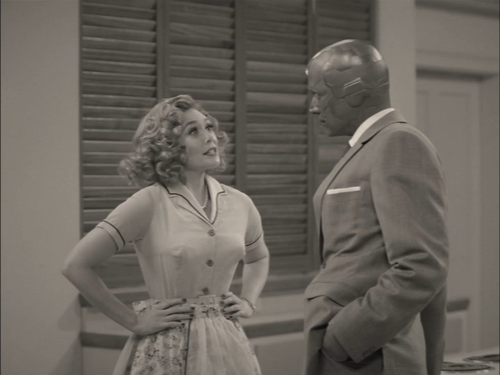 Domestic bliss? Vision and Wanda appear in WandaVision's unusual setting. Photo: from Marvel Studios/Disney+ Wandavision (2021). A black and white screenshot from the TV show Wandavision showing Wanda (a woman in a 1950s outfit) and Vision (a robotic man in a suit).