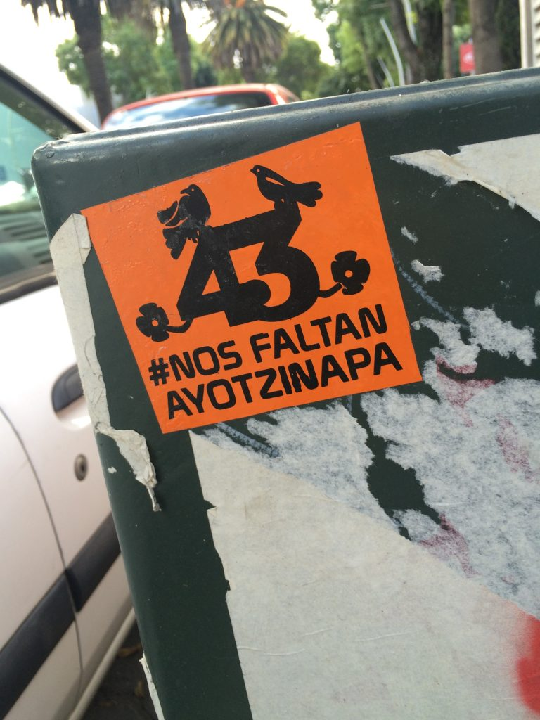 """Protest sticker on the forced disappearance of the 43 students from Ayotzinapa. An orange sticker with the words """"43 #Nos Faltan Ayotzinapa"""". Photo: Padaguan via Wikimedia Commons"""