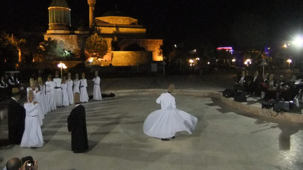 Start of Sama` at Rumi's mausoleum, photo by David Oughton. People in white costumes dance outside.
