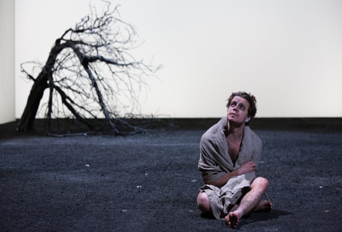 Edgar (Oliver Johnstone) sits on a blackened, ashy wasteland, contemplating a featureless sky, in the 2016 Gregory Doran production of King Lear.