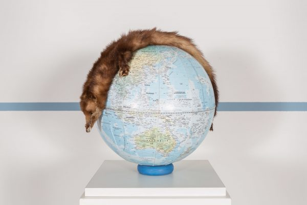 A fur rug is draped over a globe