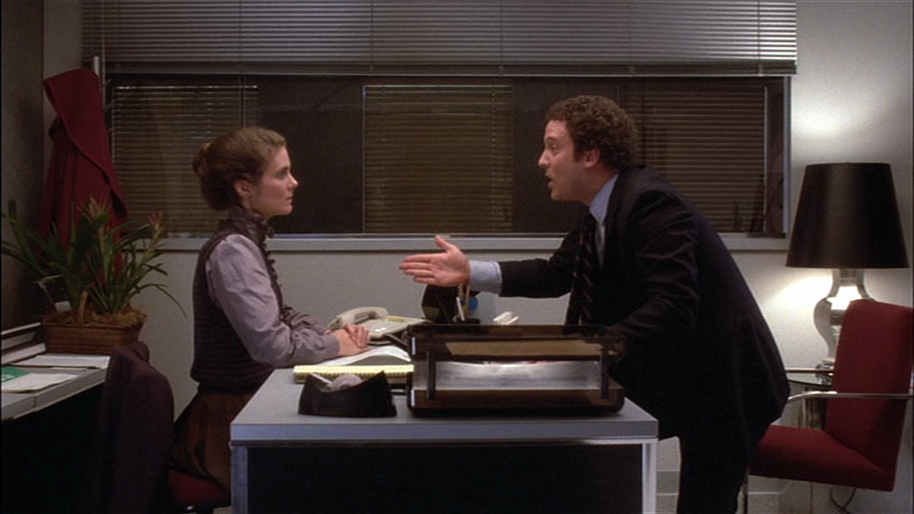 In an office setting, Albert Brooks acts opposite Julie Hagerty in a screenshot from film Lost in America (1985, dir. Albert Brooks, The Geffen Company).