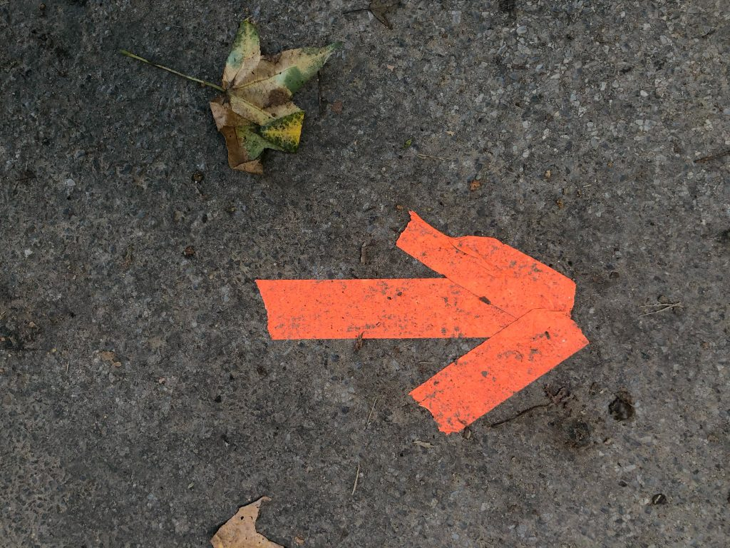Three piece of red tape stuck to the ground formed into the shape of an arrow