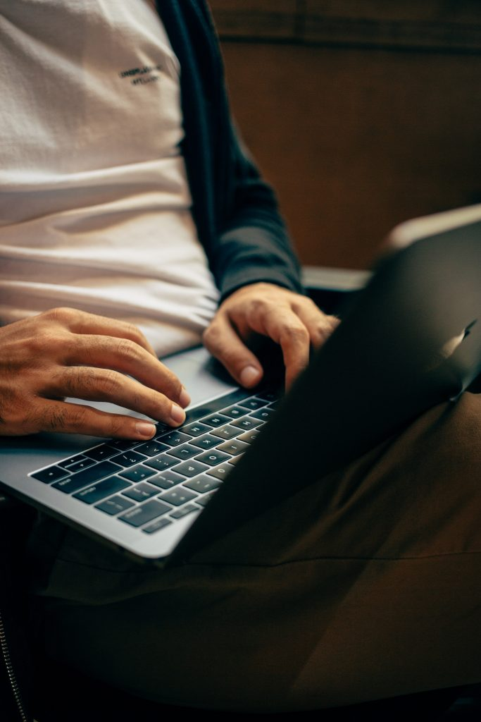 A pair of man's hands rest on a laptop