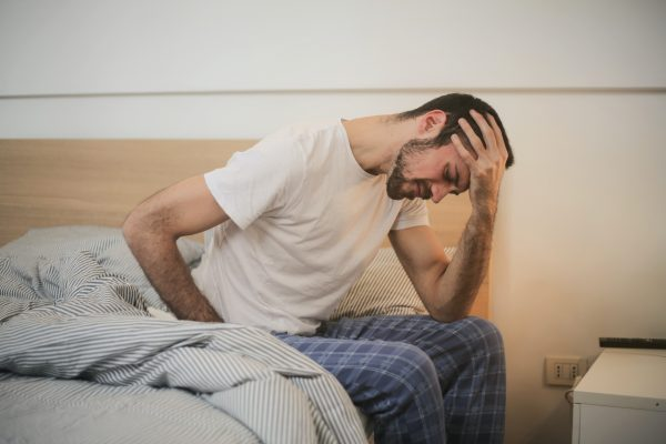 A man sits on the edge of a bed looking ashamed