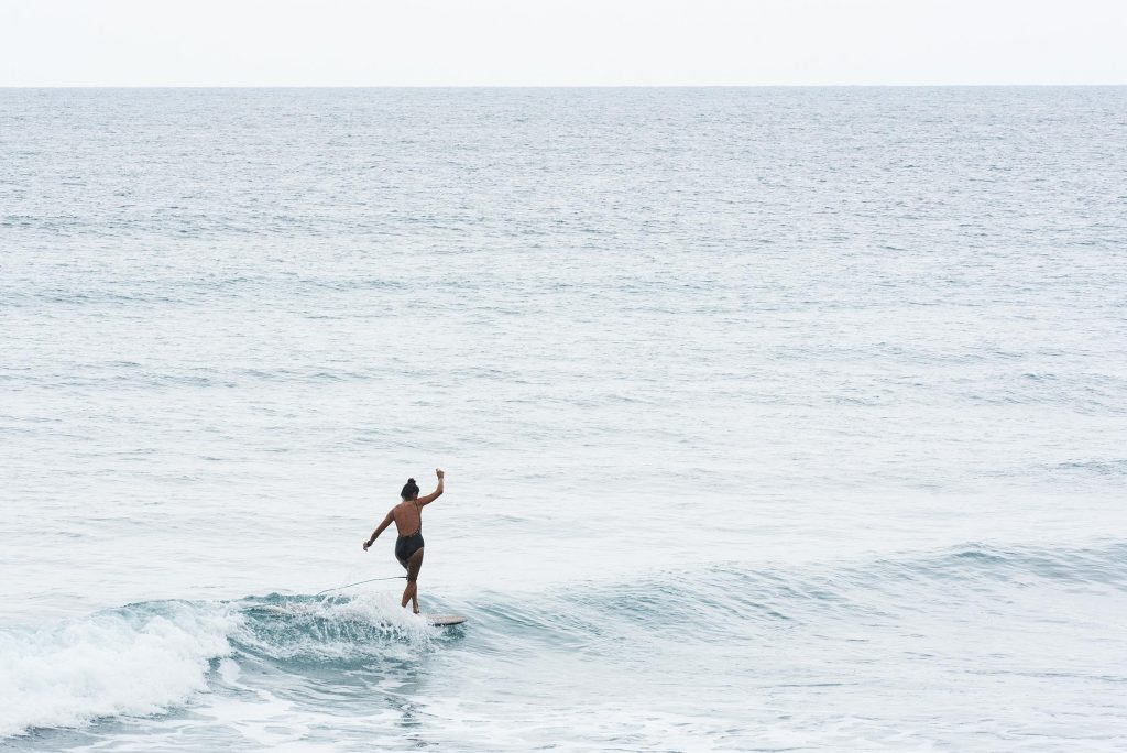 A woman is on a surfboard at sea