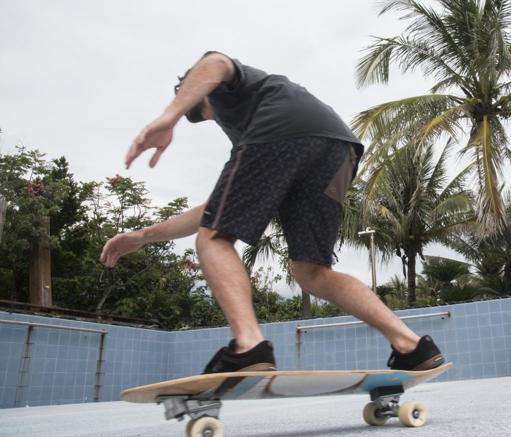 A man is on a skateboard, his back slightly bent as if preparing to do a trick