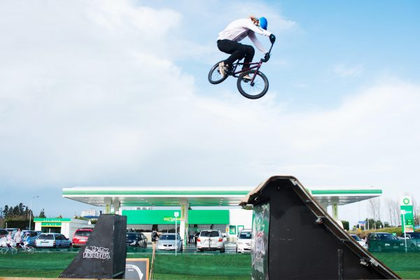 A woman on a dirt bike jumps over a ramp