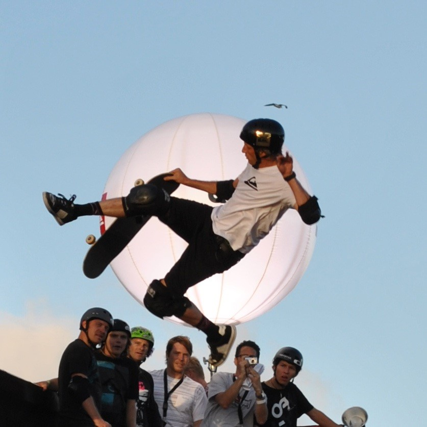 A man doing a skateboard trick in front of a crowd